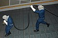 US Navy 060124-N-2736O-012 Two members from the at sea fire party pull an Aqueous Film Forming Foam (AFFF) hose to the scene of a fire aboard the transport dock ship USS San Antonio (LPD 17) during a general quarters drill.jpg