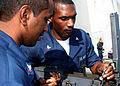 US Navy 081127-N-6764G-014 Personnel Specialist 3rd Class Timothy Sidial and Fire Controlman 3rd Class Rodregous Johnson perform maintenance on a .50 caliber machine gun.jpg