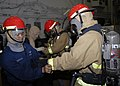 US Navy 090417-N-9520G-006 Aviation Support Equipment Technician 2nd Class Phil Y. Degracia, from Downey, Calif. assigned to amphibious assault ship USS Essex (LHD 2), assists a Sailor with his fire fighting gear during a genera.jpg