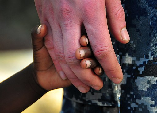 US Navy 100123-N-4774B-840 Ensign Adam Cole holds hands with a Haitian girl during an assessment visit