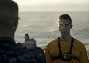 US Navy 111224-N-DR144-121 Mass Communication Specialist 3rd Class Aaron Shelley captures video footage from a camera mounted to his chest as he is.jpg