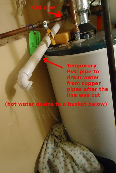 File:White pipe to temporarily drain water into large bucket.jpg
