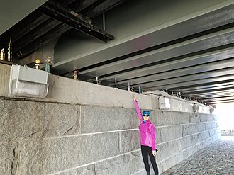 Longfellow Bridge - Woman adds trophy to collection under the Longfellow Bridge in Cambridge, Massachusetts.