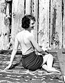 Woman in a swimsuit sitting on a blanket in front of a log fence, probably Washington State (4724938830).jpg