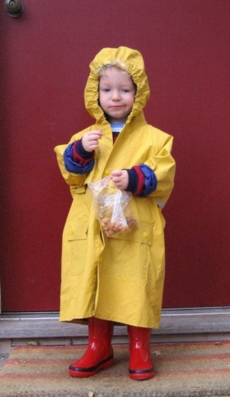 Raincoat - A child wearing a yellow raincoat with hood