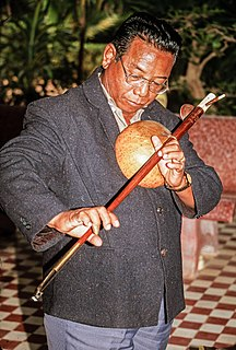 Kse diev Cambodian bar zither, has calabash gourd for resonator, bronze string connected to instrument by tuning peg and upturned end of instrument.