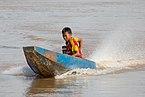 Young boy driving a motorized pirogue.jpg