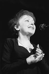 Photo of Édith Piaf at the microphone.