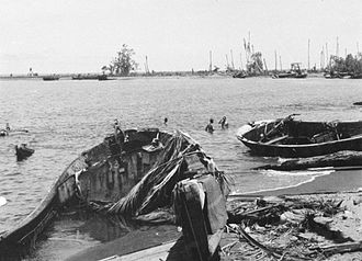Battle of Buna–Gona: Japanese forces and order of battle - Derelict Japanese barges on the beach near Sanananda after its capture.  Barges were used to resupply the coastal defences.  Allied soldiers are enjoying a swim in background.  AWM030258