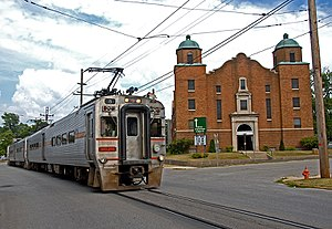 Silver single-level electric passenger train on the street in front of a brick church in Michigan City, Indiana