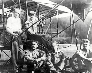 John Henry Towers - Early Naval Aviators: Towers is seated second from left. Glenn Curtiss at controls. Theodore Ellyson at the nose wheel of the plane.