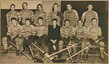 A black and white photo of ice hockey players sitting in two rows on a bench, with their coach in the middle front row.
