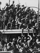 Cheering soldiers sitting and standing aboard the deck of a departing ship