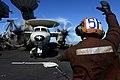 A Sailor signals the pilots of an E-2C. (8468330554).jpg