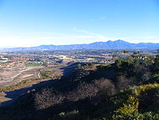 A small stream winds past in the lower left foreground while residential subdivisions sprawl over the hills on both sides. Mountains rise in the distance beneath an empty, pale blue sky.