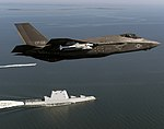 An F-35 Lightning II completes a flyover of USS Zumwalt (DDG 1000). (29774535153).jpg