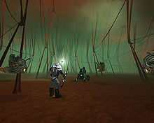 An armored man holding a sword-like object standing in a large, foggy room filled with thick strands extending from floor to ceiling. Three floating creatures and one dead creature surround him.