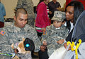 Army Sgt. Joseph Calleja, from 727th Military Police (Law and Order) Detachment, New York National Guard, presents his 2-year-old son Joseph Jr., center, and his wife Yahaira, right, with a toy Soldier 111127-A-NU174-012.jpg