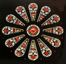 a small round stained glass window surrounded by twelve panels featuring floral designs of large red and small white flowers