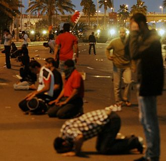 Death of Abdulredha Buhmaid - Protesters performing Maghrib prayer in front of the army.