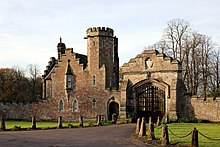 A gatehouse with a tower and a gateway to the right, all battlemented