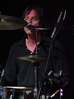 The drummer in a close-up view through the gaps between his drums and cymbals. His face and neck are slightly reddened from his exertion. While drumming, he is singing into the microphone mounted close to his face
