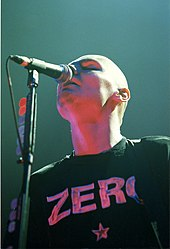 "Billy Corgan is depicted from a worm's eye view as he sings into a microphone. He is wearing one of his black ""ZERO"" t-shirts with lettering and a five-pointed star in reflective silver."