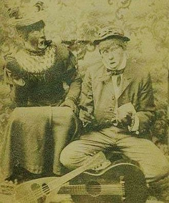Blackface - This postcard, published c. 1908, shows a white minstrel team. While both are wearing wigs, the man on the left is in blackface and drag.