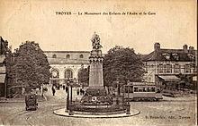 Carte postale ancienne montrant une motrice du tramway de Troyes derrière le monument des Enfants de l'Aube, et, en arrière-plan, la gare