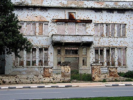 Building in Huambo showing the effects of war Building with Bullet-holes in Huambo, Angola.jpg