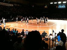 A flat wooden surface with roller skaters wearing helmets and knee pads standing on it. Some are wearing black and white striped shirts. People sit on the ground surrounding it and in bleachers.
