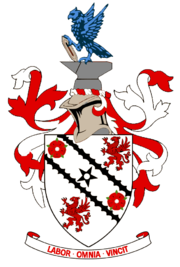 """A white shield upon which emblems of two red roses and two red griffins appear at alternate corners. A black five-pointed star is in the centre of the shield's design between two black diagonal lines. Around the shield are red and white ribbons in a symmetrical design. Above the shield is a silver-coloured knight's helmet surmounted by grey anvil upon which a vivid azure-coloured eagle is perched, holding a grey shuttle. Below the shield is the motto """"LABOR OMNIA VINCIT""""."""