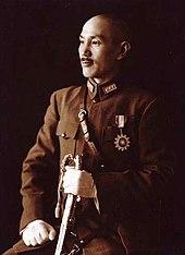 Китаец в военной форме, улыбаясь и глядя в левую сторону.  Он держит меч в левой руке и имеет медаль в форме солнца на его груди.