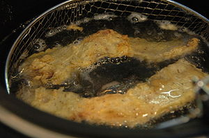 Chicken fried bacon - Homemade chicken fried bacon frying in a pan
