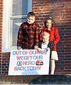 Children wait for their father, U.S. Army Sgt. Harry May, with the 198th Expeditionary Signal Battalion, Delaware Army National Guard, to return home from yearlong deployment to Afghanistan in Georgetown, Del 140226-Z-ZB970-004.jpg