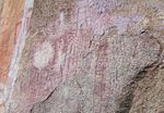 A picture of various red markings on a stone wall.