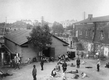 A vantage point picture of a prison camp at the Suomenlinna Fortress in Helsinki. Around 25 Red prisoners are present in the courtyard, surrounded by a shack and a garrison building.