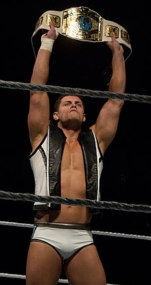 A Caucasian male wearing short, white, wrestling tights and a white and black jacket holds a wrestling championship in the air above his head. The championship consists of five visible gold plates afixed to a white strap.