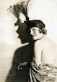 Woman with feather hat, looking over shoulder