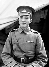 Half-length outdoor portrait of young man in military uniform and peaked cap, with pilot's wings on left breast pocket