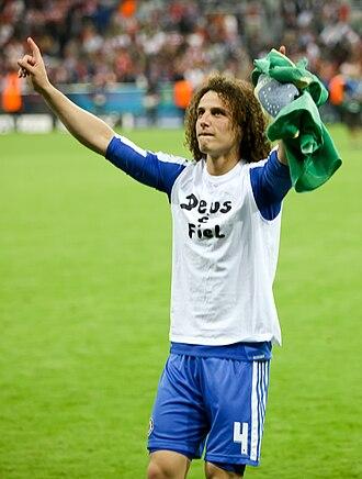 """David Luiz - David Luiz with a T-shirt saying """"Deus é fiel"""" (""""God is faithful"""") after winning the Champions League"""