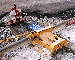 Derail device installed at an industrial site, complete with blue flag ...: https://en.wikipedia.org/wiki/Derail