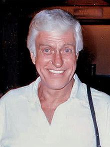 A white-haired man wearing a suit, smiles at the camera