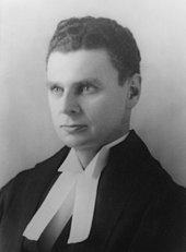 Diefenbaker with an intense look in his eyes. Still a young man, he wears ceremonial robes in this portrait shot; the bands of the robes are visible.