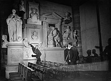 Director Humphrey Jennings stretches to touch a piece of sculpture in Poets' Corner in Westminster Abbey, as he suggests a shot for camera operator Chick Fowle of the Crown Film Unit in January 1941. D1861.jpg