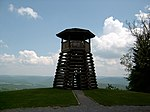 A wooden observation tower overlooking a forested valley.