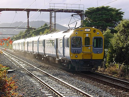 Two of Tranz Metro's EM class electric multiple units working a southbound morning service on the Hutt Valley Line. EM 1367 leading a southbound 4 car set as the morning sun breaks through the clouds, near Epuni - 17 May 2003.jpg