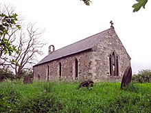 A photograph of a small stone church with open, glass-less windows. The church is surrounded by rough, uncultivated ground and the sky behind the church is bleak.