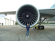 Aircraft engine, forward-facing view with a Boeing engineer in front to demonstrate the engine's size. The engine's large circular intake contains a center hub with a swirl mark, surrounded by multiple curved fan blades.