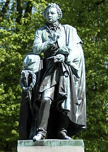 Esaias Tegnér statue near the towering Lund Cathedral .